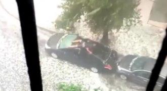 Απελπισμένος άνθρωπος προσπαθεί να προστατεύσει το αυτοκίνητό του από το χαλάζι.