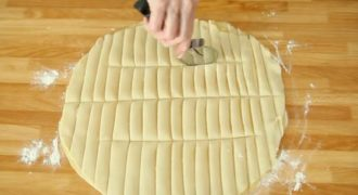 Χρησιμοποιώντας ένα «μαχαίρι» για πίτσα, Κόβει την ζύμη σε λωρίδες. Στο τέλος…